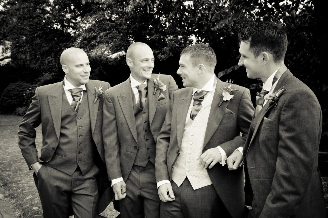 black and white photo of groom outside church on wedding day.