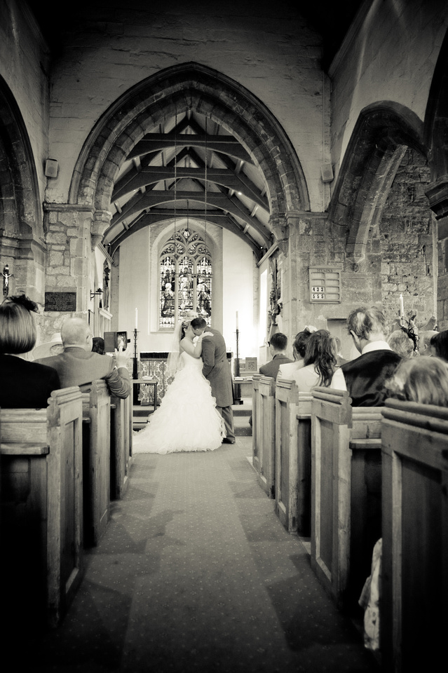 black and white photograph of bride and groom kissing during their wedding in Rotherham