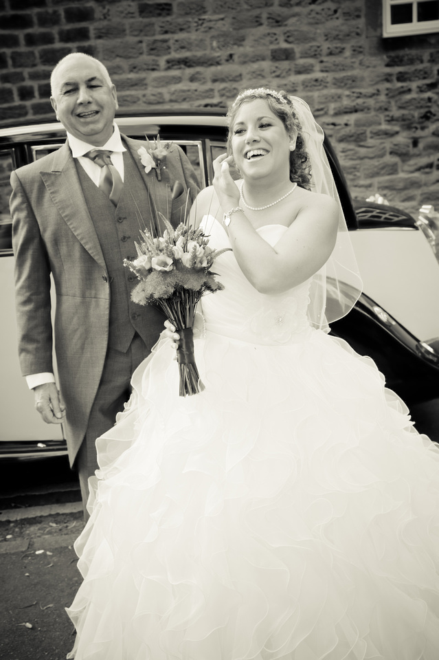 black and white wedding photograph of bride arriving at church