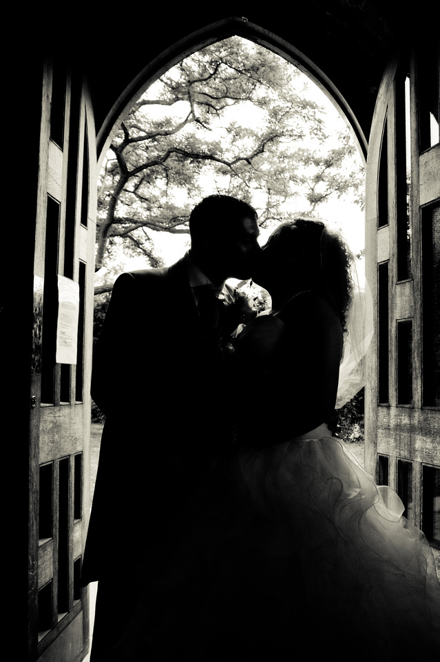 black and white wedding photograph of bride and groom kissing in church door.
