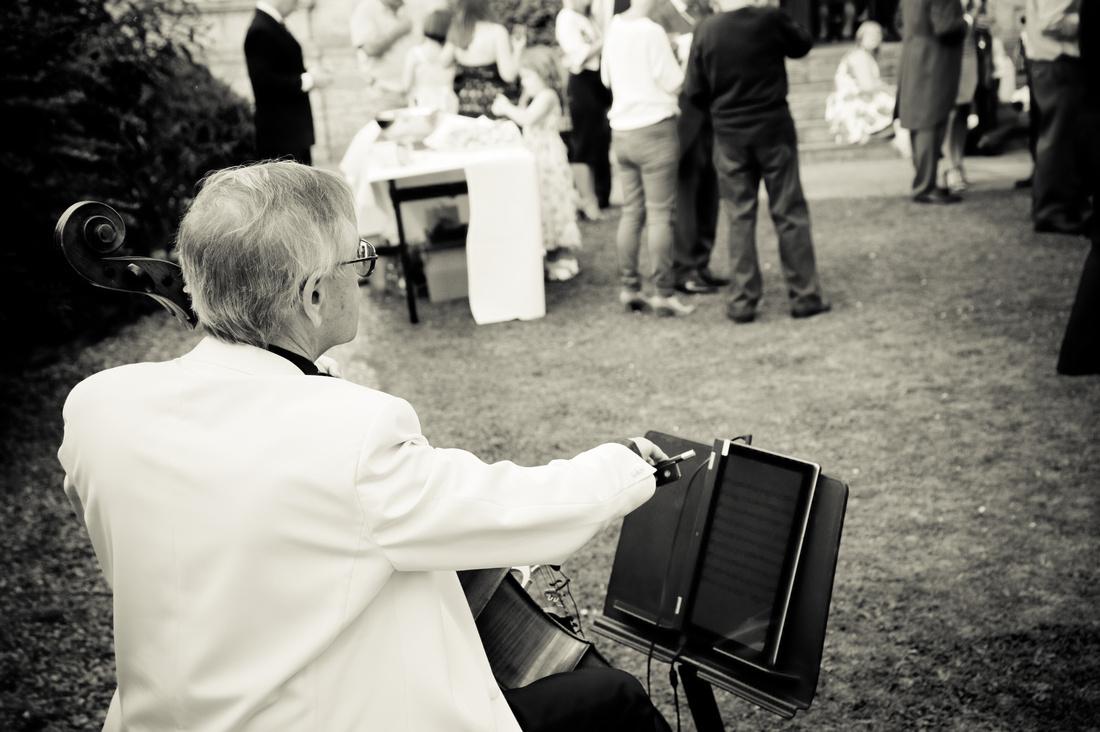 black and white wedding photo of cellist