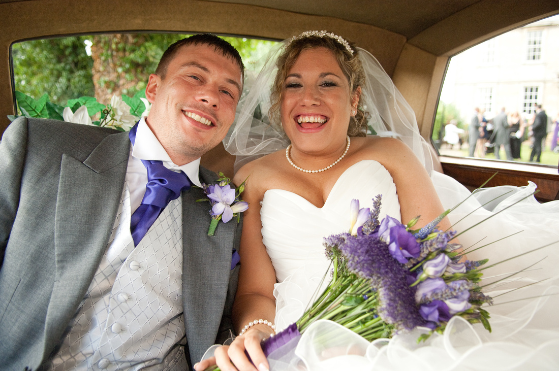 photograph of bride and groom in their wedding car